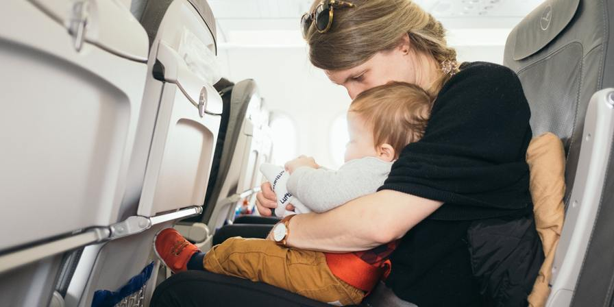 A woman sitting on a plane with a child on her lap