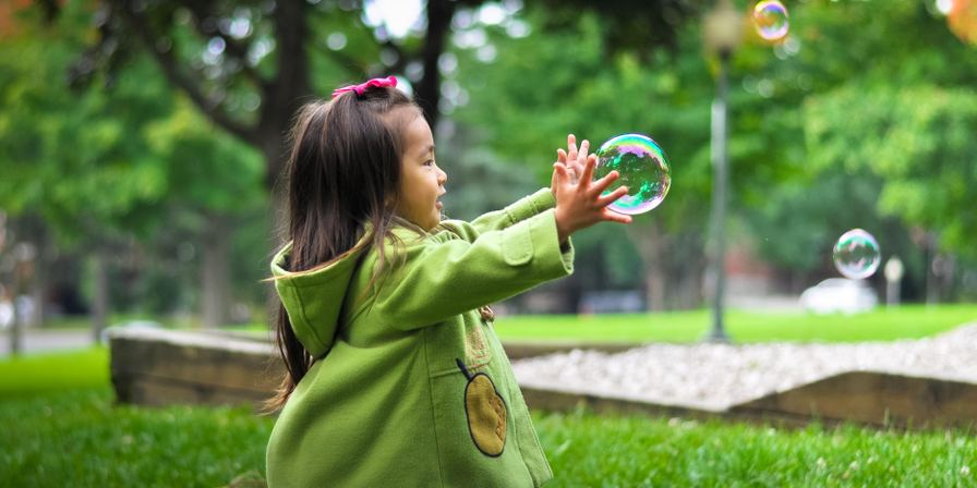 A young girl playing with bubbles