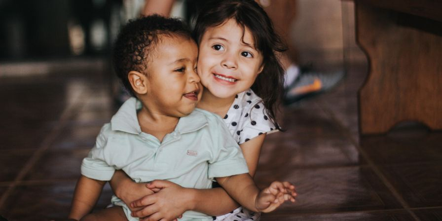 An older girl with a younger boy sitting on her lap, with her arms wrapped around him