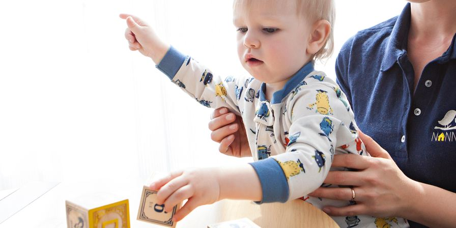 child playing building blocks while held by caregiver