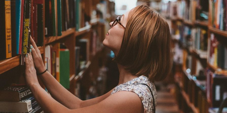 Woman with her hands on a bookshelf in a library