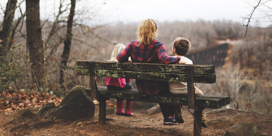 A woman and two children sitting on a bench