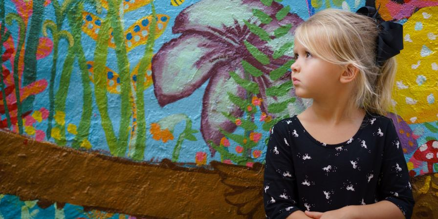 A young girl posing in front of a wall painted with a colorful flower