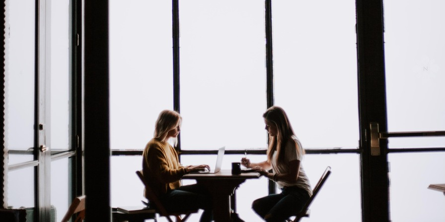 Two women sitting at a desk, one looking at her laptop screen and the other jotting down notes