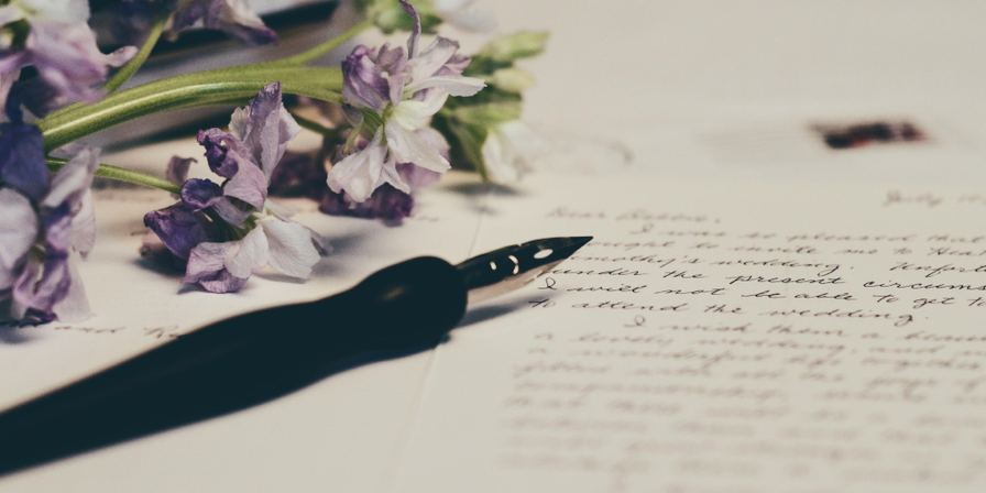 Calligraphy pen set down on a piece of paper with cursive writing on it