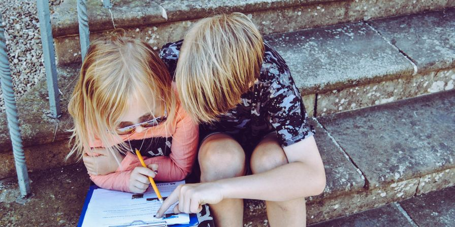 Two children huddled together writing in a notebook