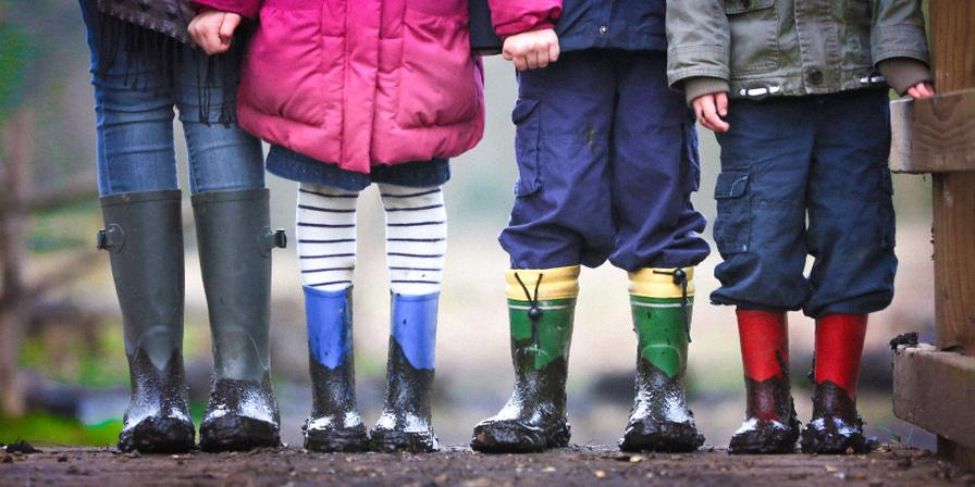 Three children and an adult standing in rainboots
