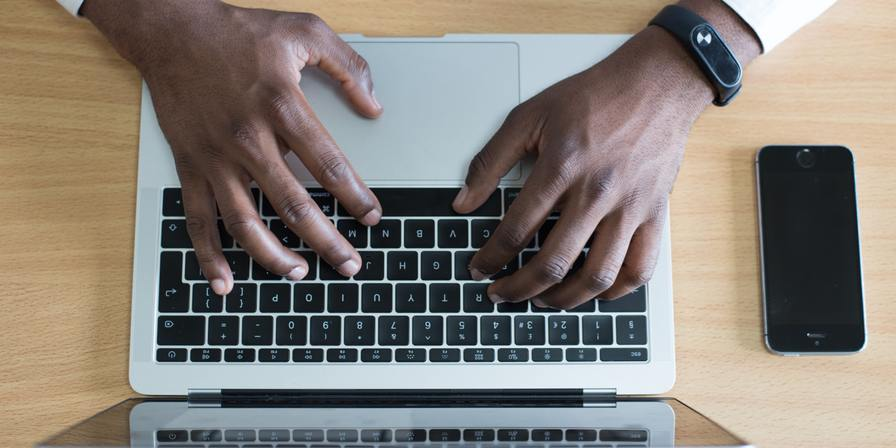 Hands on their laptop keyboard