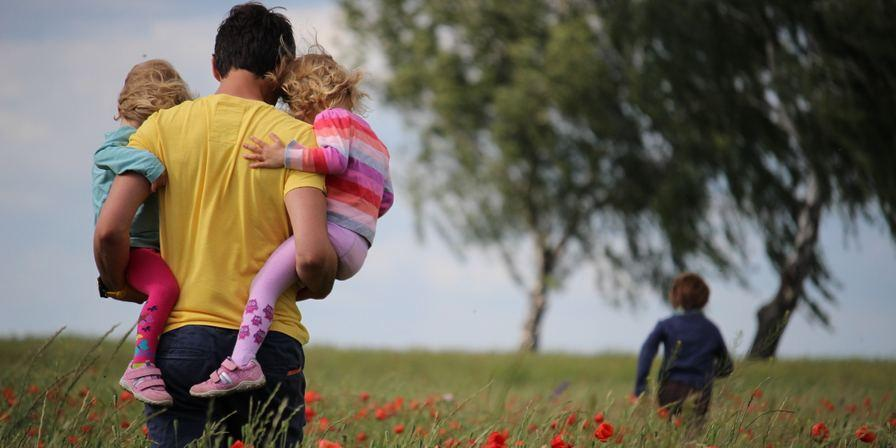 an adult carrying two children in their arms as they walk through a field of flowers
