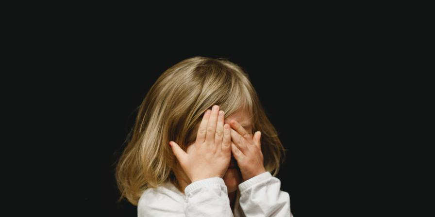 A child covering their face with their hands