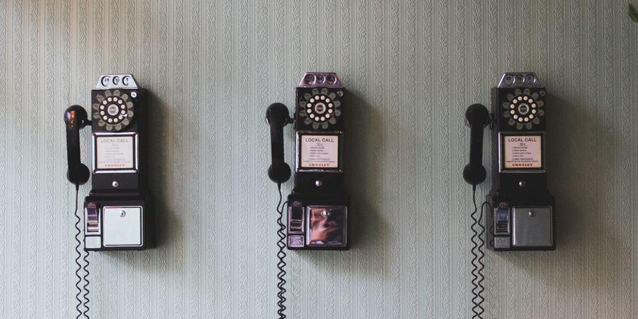 Three old-fashioned phones on a wall