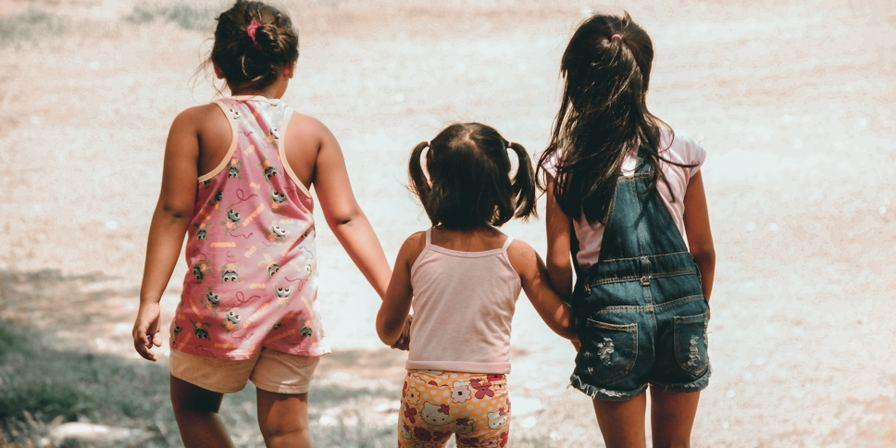 Three kids holding hands while looking out at the tide on a beach