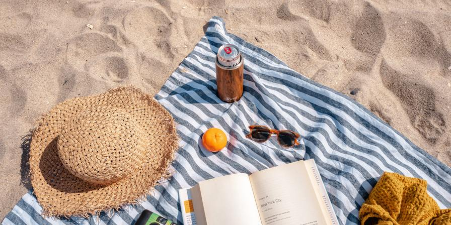 A towel, book, snack and drink on a beach