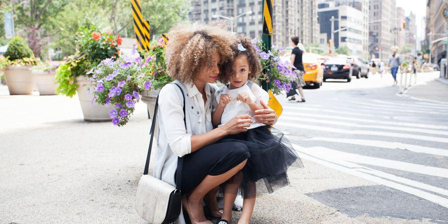 A woman and child playing on the sidewalk