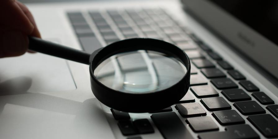 A magnifying glass and a laptop keyboard