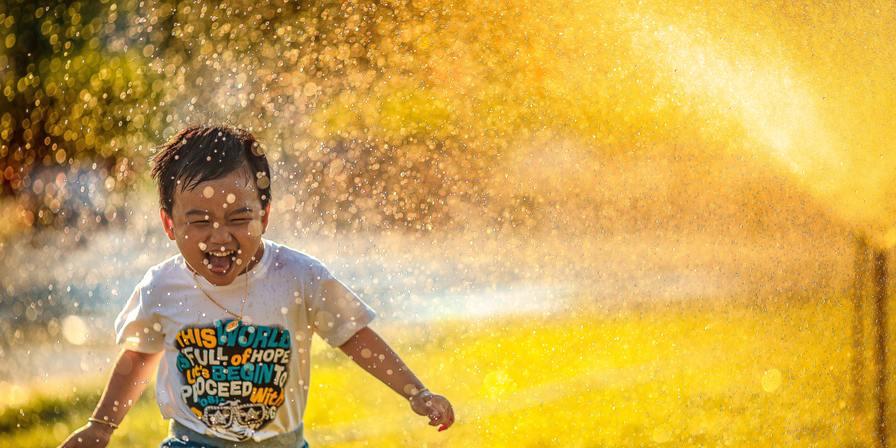 A child running through a sprinkler