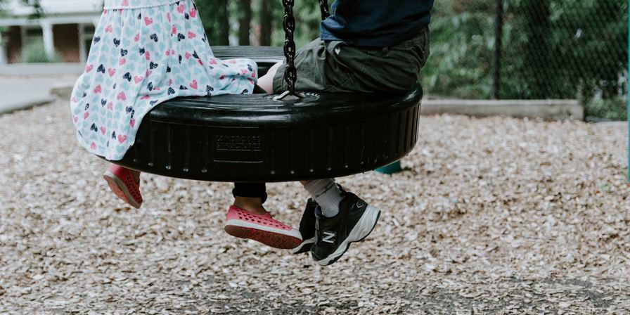 A boy and a girl sitting on a tire swing that is hanging