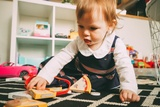 Young toddler playing with plastic pizza slice toys on a carpet