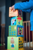 Young child stacking very large colorful blocks