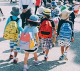 Four children walking in line, wearing backpacks and hats