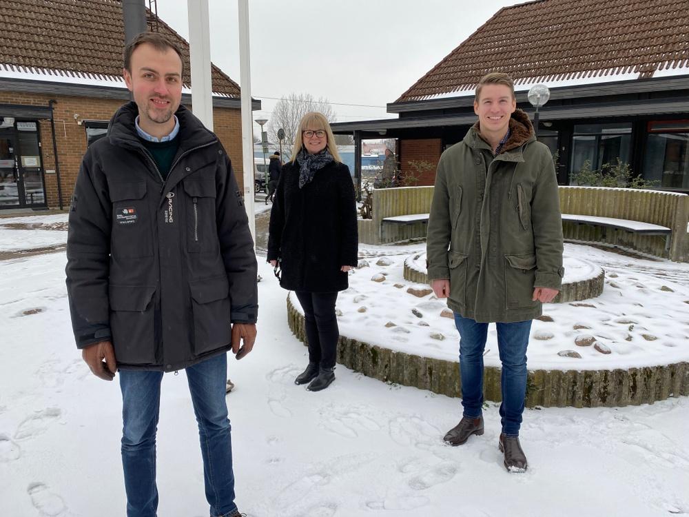 Tre personer grupperade utomhus med smittsäkert avstånd