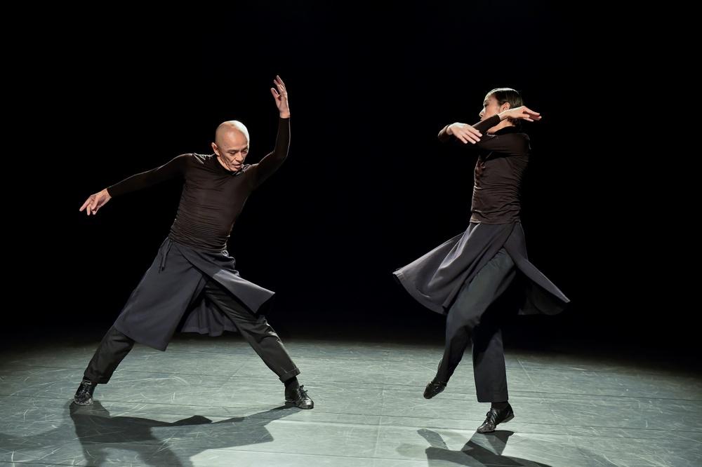 Två dansare står i svarta kläder på en avskalad svart scen. Båda har långa rockar som böljar kring benen. Det är en äldre man cirka 65 år, och en kvinna i medelåldern. Mannen slår kraftfullt ut med armarna.