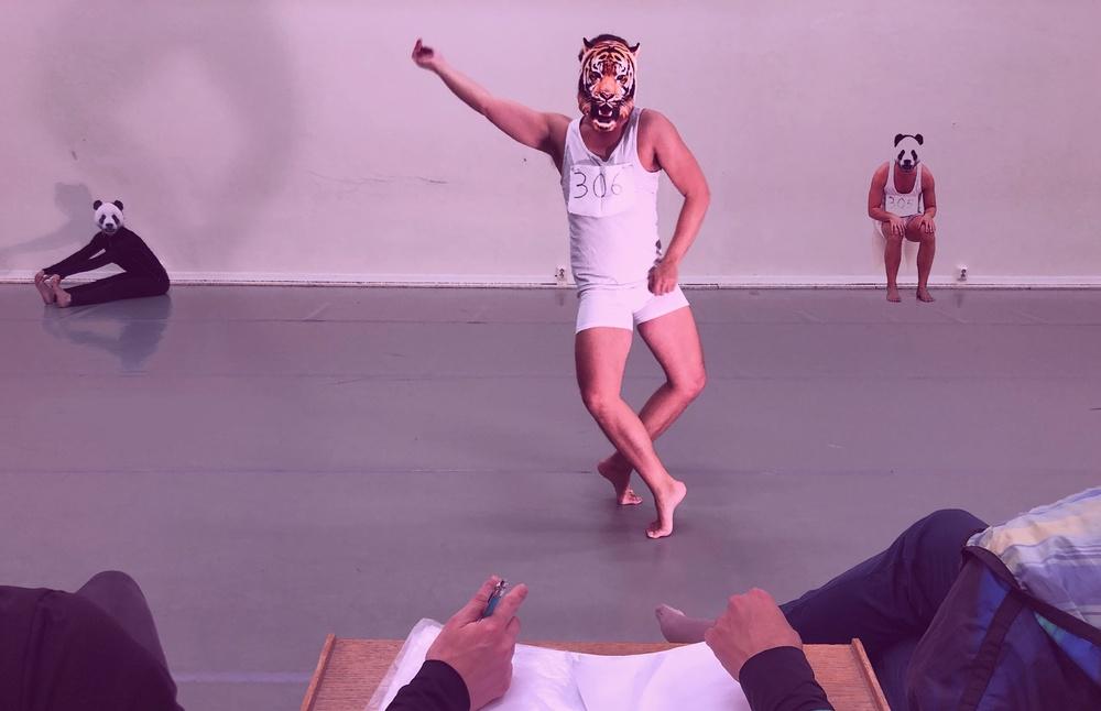 En dansare i vitt linne och vita shorts med en tigermask på huvudet, står i mitten av ett dansgolv. I bakgrunden sitter två dansare mot väggen med pandamasker.