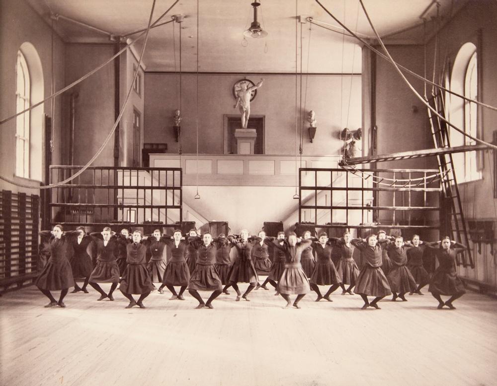 """Linggymnastik för kvinnor vid Gymnastiska Centralinstitutet (GCI) i Stockholm omkring 1892. Övningen """"Vilnigstående utgångsställning"""".  Ling var starkt influerad av rådande antika ideal. Kroppen skulle präglas av harmoni och symmetri. Kontroll och disciplin var en del av detta och ansågs som viktiga manliga egenskaper. Lika noga med träning var det inte för kvinnorna. De behövde visserligen träning, men i första hand för att klara av att föda barn. Kvinnorna fick heller inte träna så mycket att deras kvinnliga, runda former """"förmanligades.""""  Bildkälla: Gymnastik- och idrottshögskolans bibliotek, okänd fotograf."""