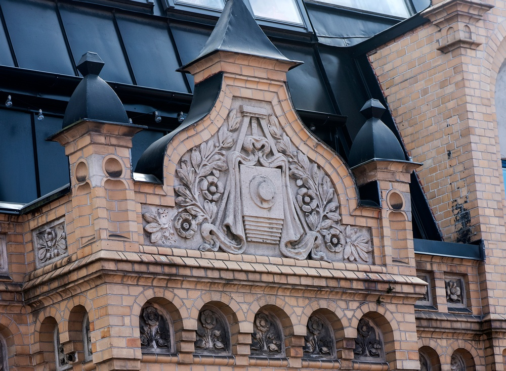 Högt upp på huset på Stora Gråbrödersgatan 12 finns en kamera med stativ och skynke, huggen i sten. Foto: Viveca Oholsson/Kulturen