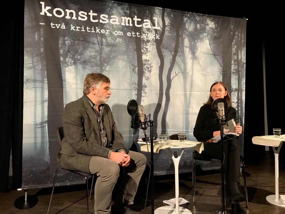 Krikerna Erik Andersson och Ylva Lagercrantz Spindler sitter på en scen med mikrofoner framför sig.