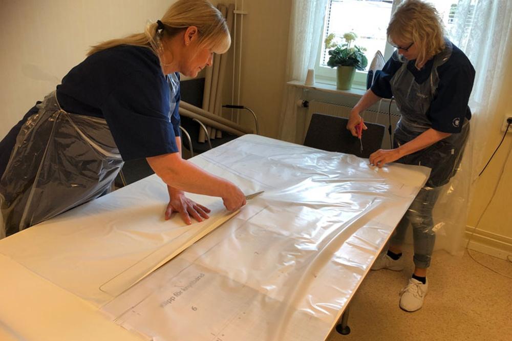 Två kvinnor klipper till plast som ska bli förkläden