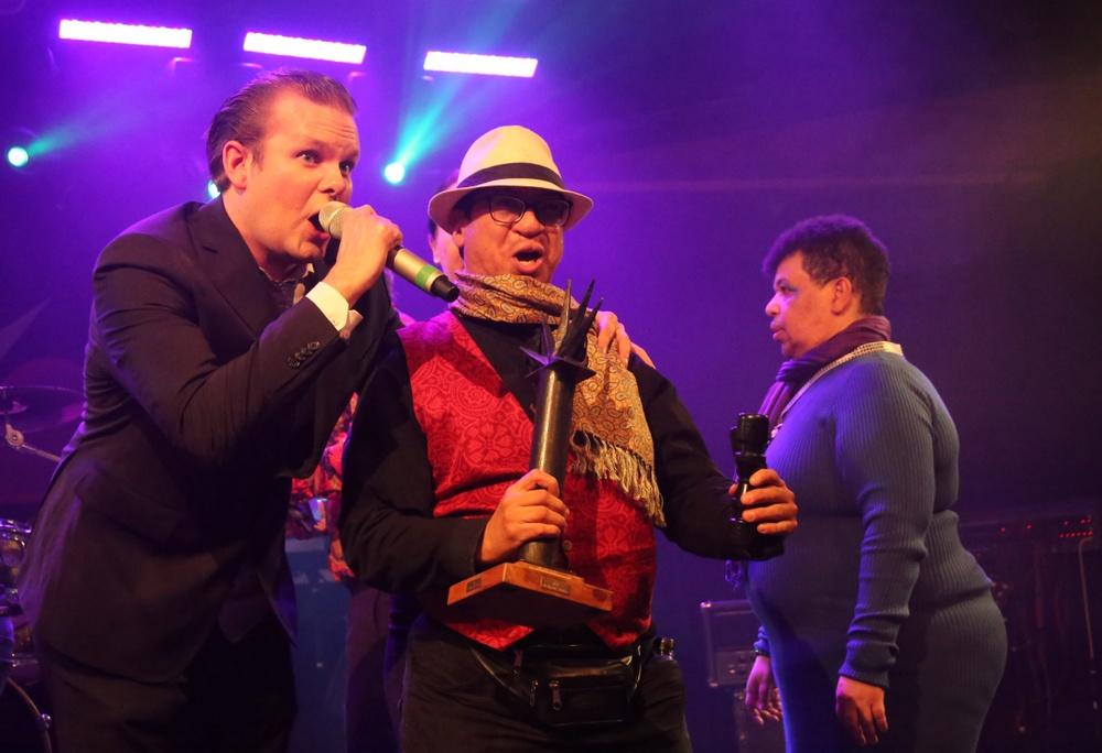 Tomas Fogelholm, Mr Positive jublar på scenen med vinnaren Santiago efter att Santiago Rubio & Big Blue Band utropats som vinnare i Musikschlaget 2019 med låten Tranquilo.
