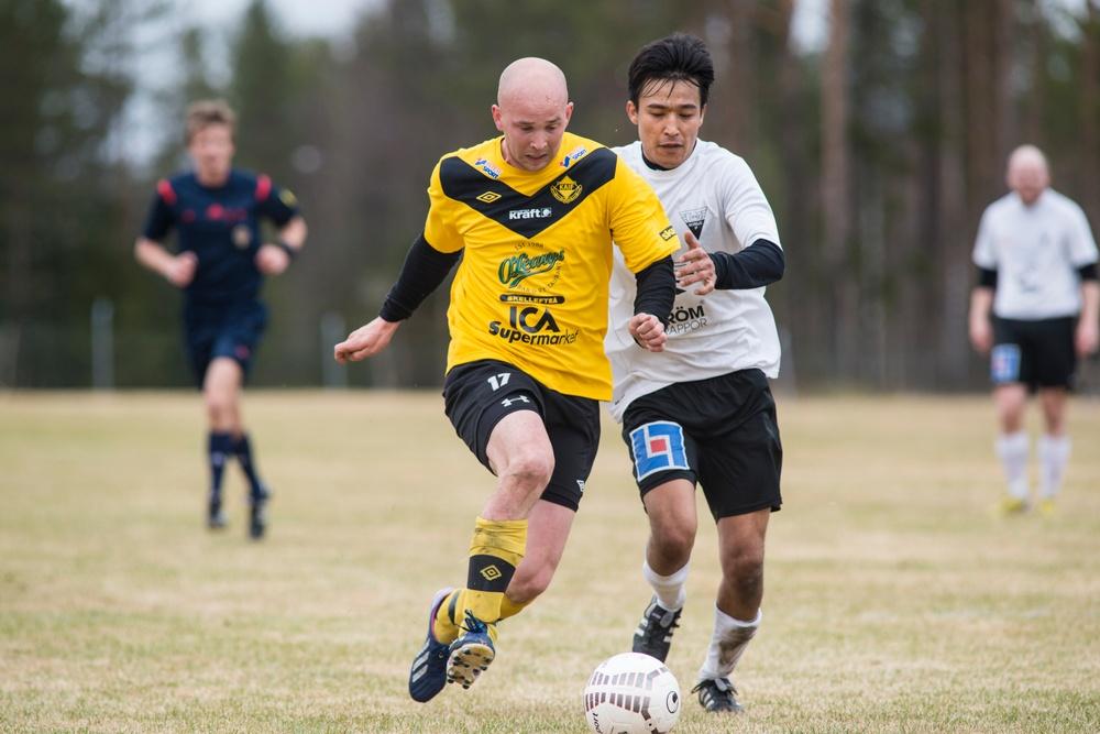 En bild från en fotbollsmatch med två personer i fokus som sparkar på samma boll