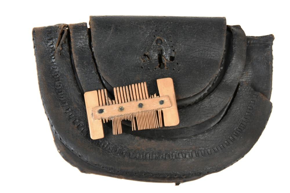 1984 påträffades denna läderväska, tillverkad av hästhud med en dekorativ ram av hål på jämna avstånd, vari ett läderband trätts. Väskor brukade fästas i ett bälte och innehöll personliga ägodelar. Just denna väska innehöll en kam. Fyndet påträffades i en brunn, där det bevarats under flera hundra år. Väskan med kammen är daterad till tiden 1300–1400-tal.  Foto: Nelly Hercberg, Kulturen