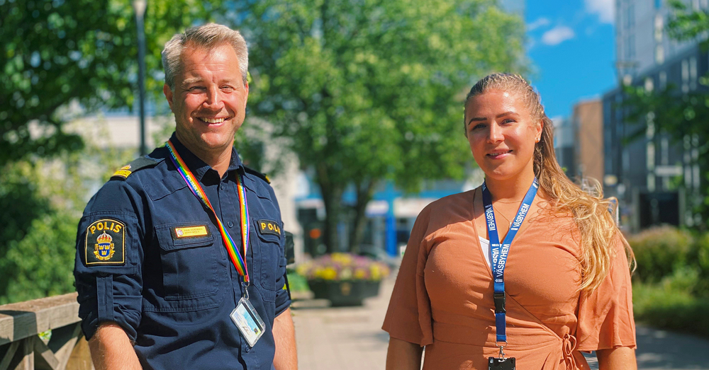 En man iklädd i polisuniform och en kvinna i orange klänning står intill ett stationsområde med mycket grönska i bakgrunden.