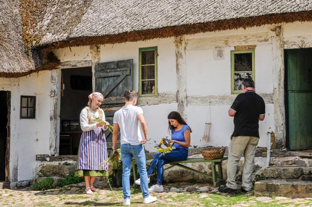 Besökare får prova på att binda kransar på Gamlegårds innergård. Foto: Viveca Ohlsson, Kulturen