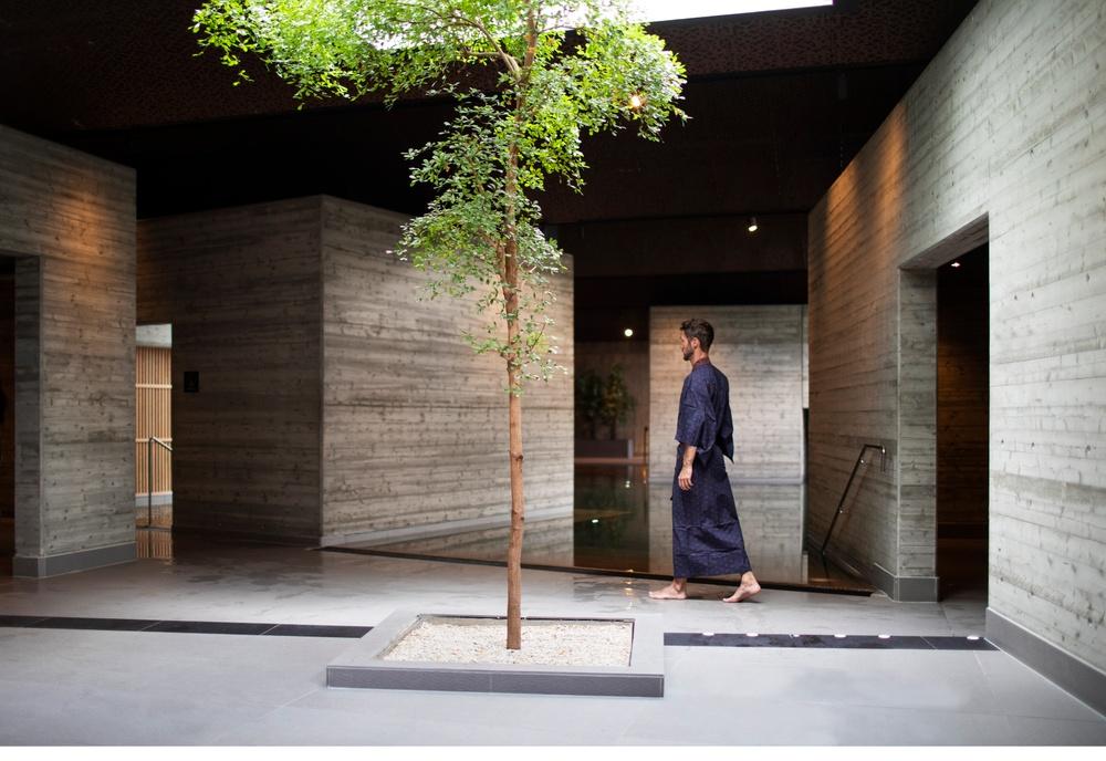 Man klädd i yukata går vid poolkanten i det japanska badet. Ett träd syns i förgrunden och man skymtar de olika betonghusen som utgör en del av badet.