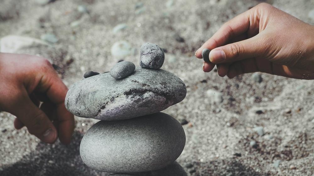 Händer som skapar en liten hög med stenar