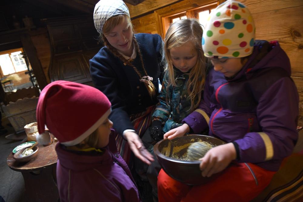 Besökande barn provar att mala senap med kanonkula i Blekingegården på Kulturen i Lund. Foto: Nelly Hercberg. Kulturen