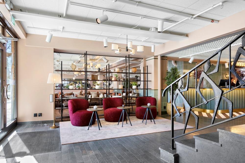 Bild på hotellobby med ett trappräcke i gjutjärn föreställande dansande personer i förgrunden