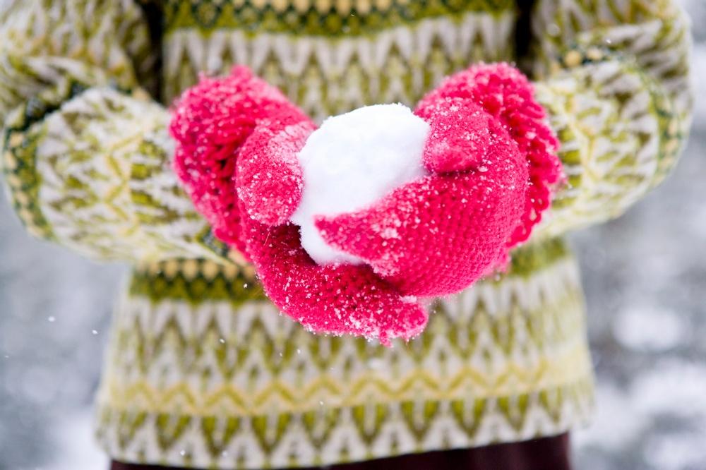 Kramar snöboll med röda vantar