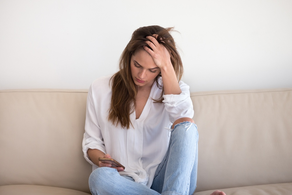 Young woman desperately looking at smartphone screen