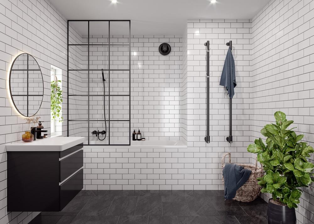 En mattsvart Pax Calima sitter på väggen i ett modernt badrum med svarta detaljer, vitt kakel och mörkt skiffergolv.