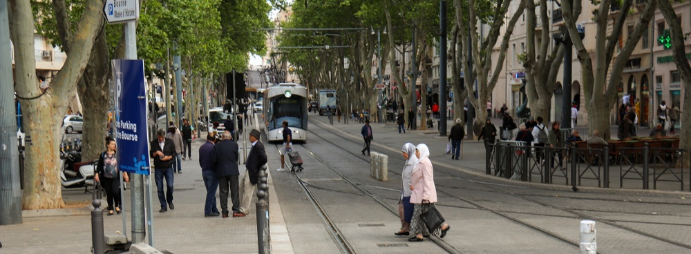 Två äldre kvinnor korsar spårvägen utan problem, medan en spårvagn står vid en hållplats i bakgrunden.