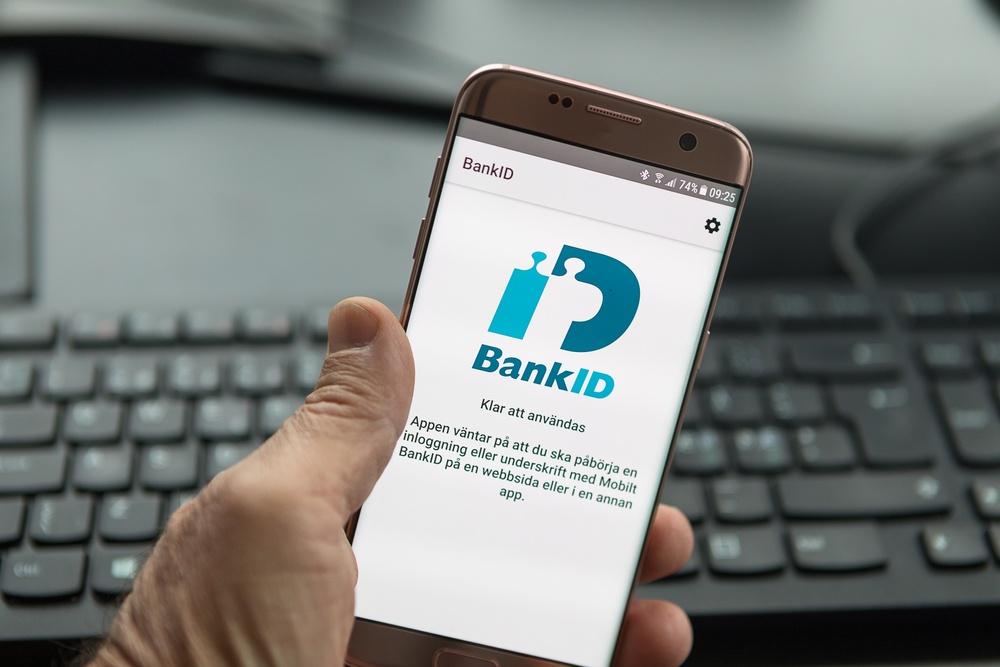 Hand som håller i en smart telefon med bank id-appen på skärmen.