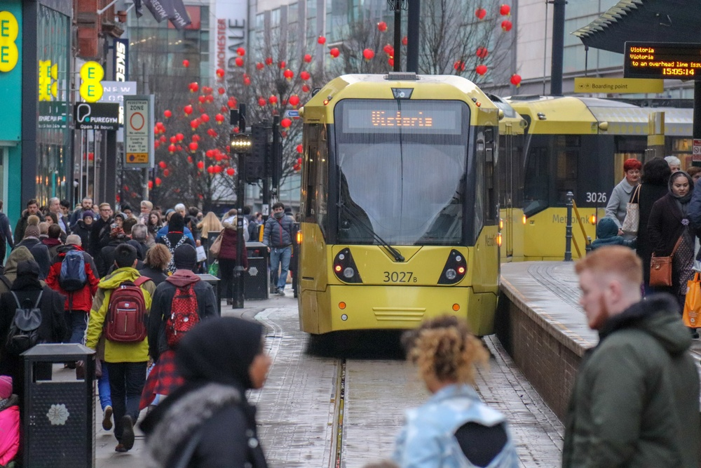Spårvagn på Manchesters gator omgiven av människor.