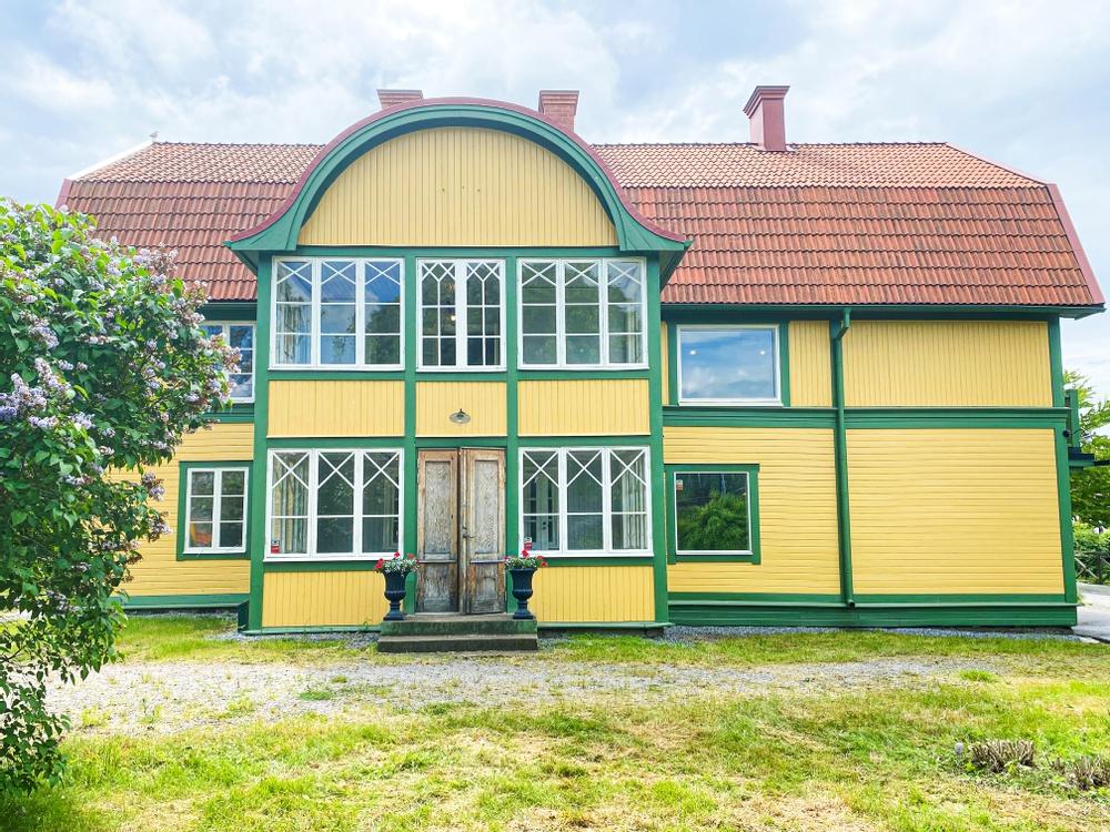 Ett äldre hus gult hus med gröna knutar från 1870-talet. Fönstren är från 1940-talet och snickerierna härstammar från olika tidsepoker. Intill entren står två blomurnor planterade med vackra röda pelargoner.