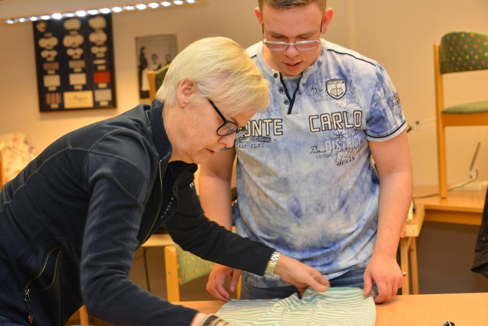 Läraren Lena Ågren och elevern Kevin Kjelvik tar hand om inlämnade kläder.