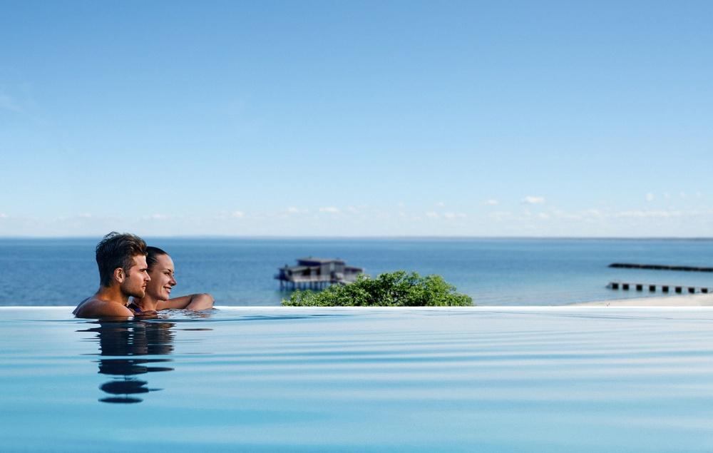 Rooftop spa bildmontage - par i horisontpool med utsikt mot Kattegatt, Skansenstranden och kallbadhuset.