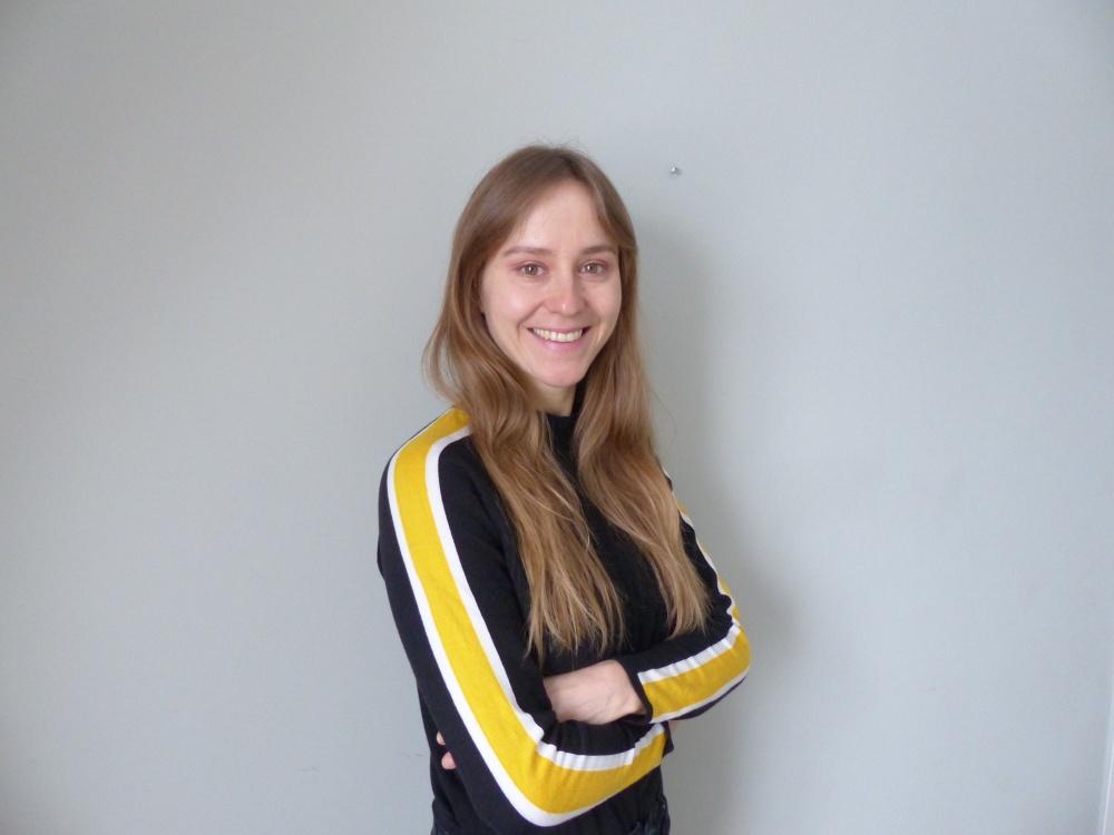 Linda Blomqvist har långt mellanblond hår och en tröja med gula revärer på sidorna. Hon ler och står mot en grå vägg.